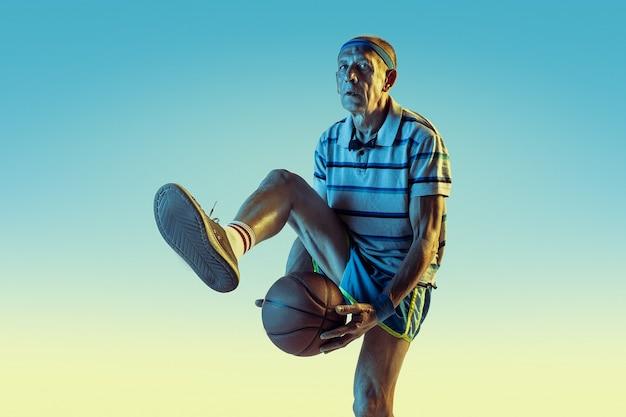 Uomo anziano che indossa abbigliamento sportivo che gioca a basket su sfondo sfumato, luce al neon. il modello maschile caucasico in ottima forma rimane attivo. concetto di sport, attività, movimento, benessere, fiducia.