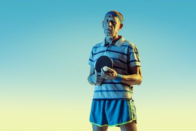 Uomo anziano che indossa abbigliamento sportivo giocando a ping pong su sfondo sfumato, luce al neon. il modello maschile caucasico in ottima forma rimane attivo. concetto di sport, attività, movimento, benessere, fiducia.