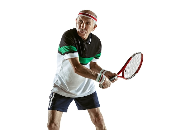 Senior uomo che indossa abbigliamento sportivo giocando a tennis isolato su sfondo bianco. il modello maschile caucasico in ottima forma rimane attivo e sportivo. concetto di sport, attività, movimento, benessere. copyspace, annuncio.