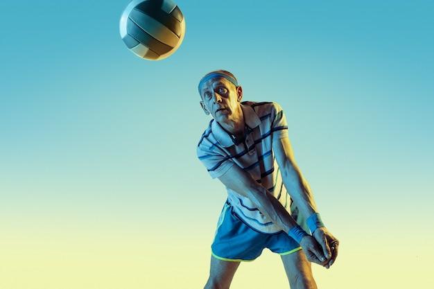 Uomo anziano che indossa abbigliamento sportivo giocando a pallavolo su sfondo sfumato, luce al neon. il modello maschile caucasico in ottima forma rimane attivo. concetto di sport, attività, movimento, benessere, fiducia.