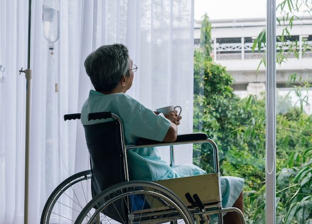 Uomo anziano in una sedia a rotelle da solo in una stanza guardando attraverso la finestra dell'ospedale