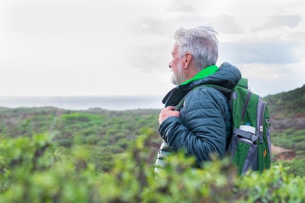 Uomo anziano con zaino in escursione all'aperto tra montagna e mare in un giorno di pioggia, guardando l'orizzonte sull'acqua