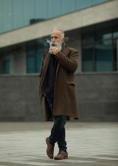 L'uomo senior con la barba espira il fumo. fumo di sigaretta elettronica. concetto di alleviare lo stress. dispositivo di fumo. uomo barba lunga rilassata con abitudine al fumo. vaping uomo barbuto. iqos.
