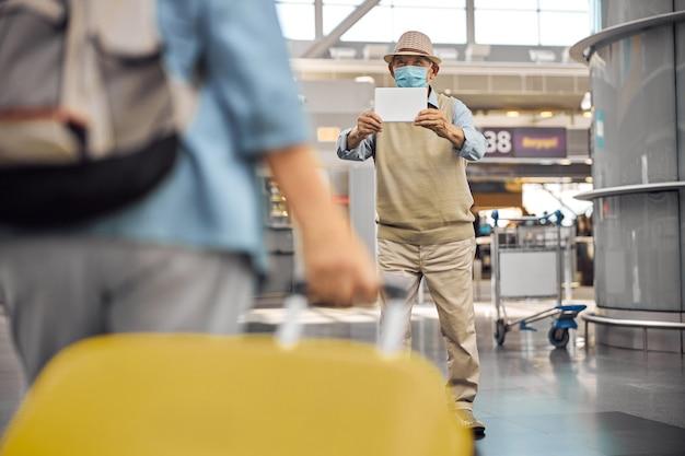 Uomo anziano con un cartello bianco in mano che incontra una donna all'aeroporto