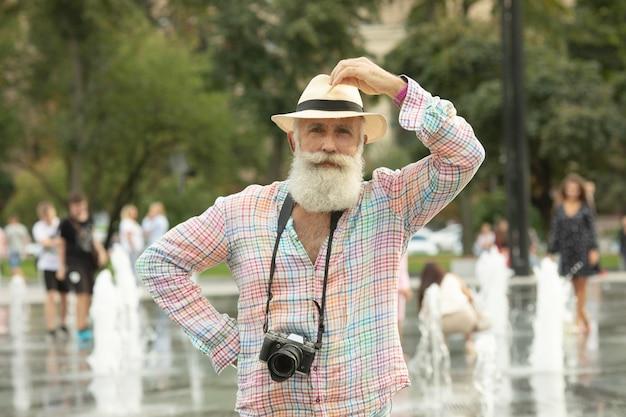 Uomo anziano con la macchina fotografica in città