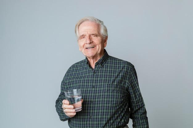 Uomo anziano con un bicchiere d'acqua
