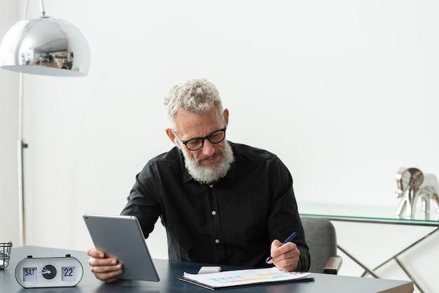 Uomo anziano con gli occhiali a casa che studia mentre usa il tablet Foto Premium