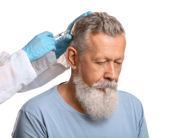Uomo maggiore con problema di perdita di capelli che riceve iniezione su bianco