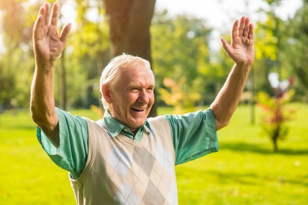Uomo anziano con le braccia alzate.