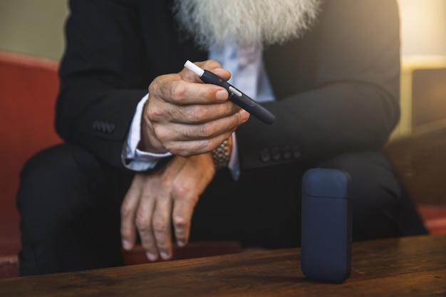 Uomo anziano con un sistema di riscaldamento del tabacco nelle sue mani