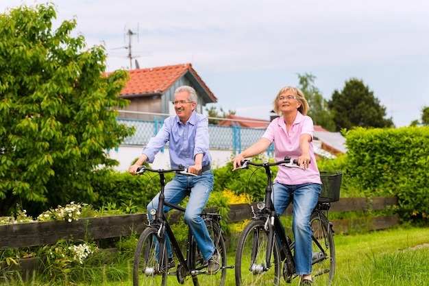 Senior uomo e donna che si esercitano con le biciclette all'aperto, sono una coppia