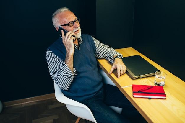 Uomo anziano che lavora nel suo ufficio.
