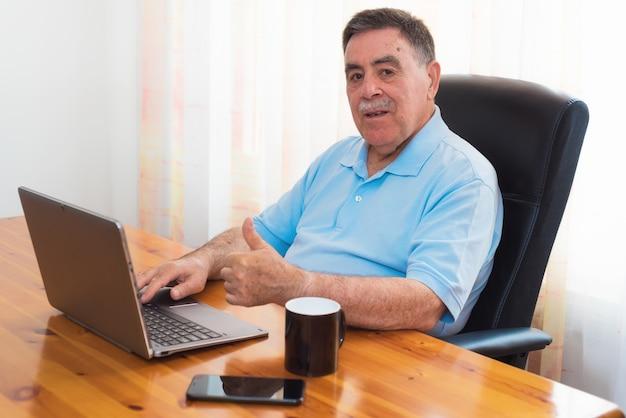 Uomo senior che lavora al computer portatile che mostra pollice in su