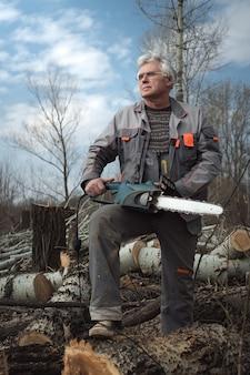 Uomo maggiore che lavora con una motosega.