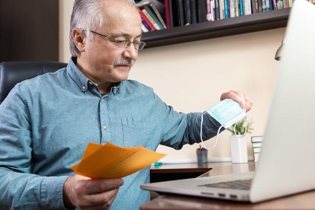 Uomo maggiore che lavora con il computer portatile a casa passando in rassegna fatture e documenti. lavoro a casa. prevenzione del coronavirus