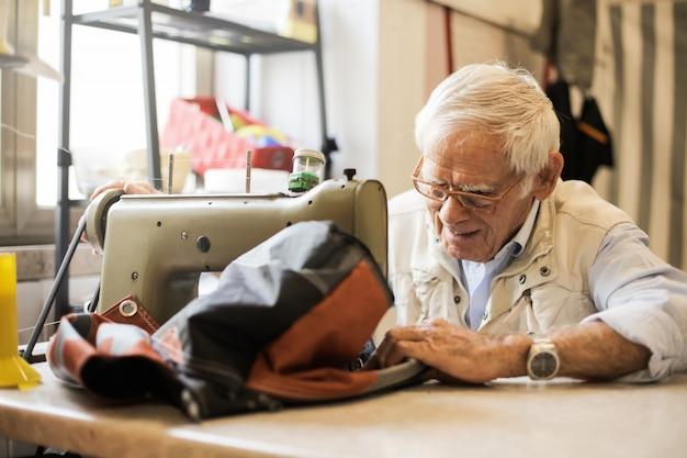 Uomo anziano che lavora con una macchina da cucire