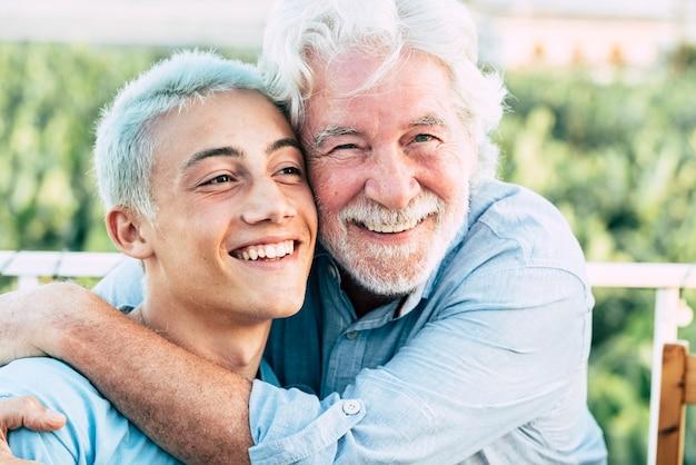 L'uomo anziano e il ragazzo si abbracciano e si godono insieme la famiglia e la bella giornata