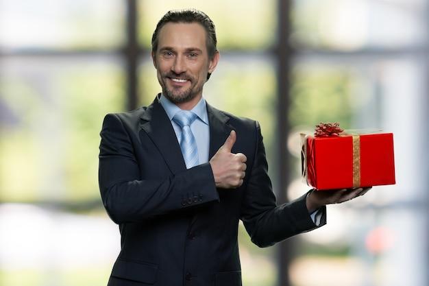 Senior manager con confezione regalo rossa e mostrando pollice in su. in piedi al chiuso, finestre sfocate sullo sfondo.