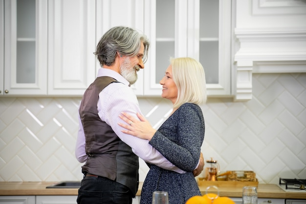 Coppia sposata senior in abiti festivi che ballano in una cucina elegante, concetto di famiglia