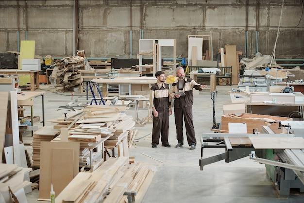 Master o caposquadra senior che indica la nuova macchina di lavorazione industriale e discute i principi del suo lavoro con il suo apprendista durante la riunione