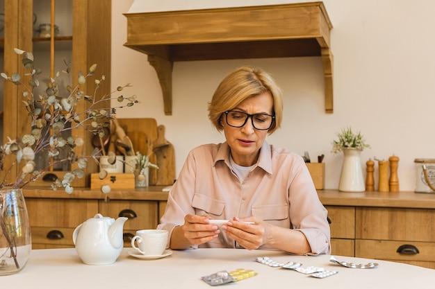 Senior donna matura con pillole che misurano la temperatura corporea con termometro medico in cucina a casa. raffreddore e influenza, coronavirus covid-19.