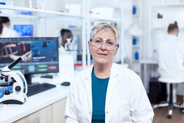 Ricerca medica senior in clinica scientifica con virus sul display del computer. scienziato anziano che indossa camice da laboratorio che lavora per sviluppare un nuovo vaccino medico con un assistente africano sullo sfondo.