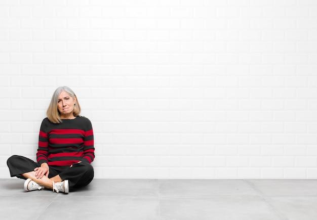 Bella donna di mezza età o di mezza età che si sente triste e stressata, sconvolta a causa di una brutta sorpresa, con uno sguardo negativo e ansioso
