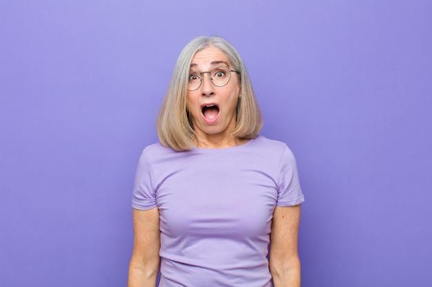 Donna graziosa di mezza età o senior che sembra molto scioccata o sorpresa, fissando con la bocca aperta dicendo wow