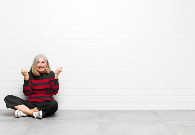 Donna graziosa di mezza età o senior che grida trionfante, ridendo e sentendosi felice ed eccitata mentre celebra il successo