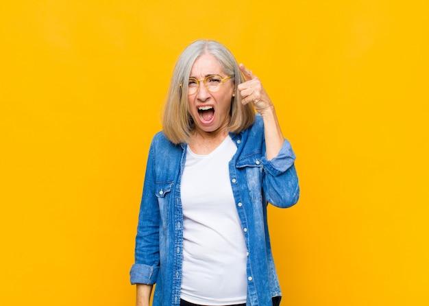 Donna graziosa di mezza età o senior con un'espressione aggressiva arrabbiata che assomiglia a un capo furioso e pazzo