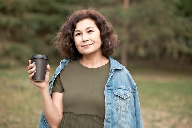 Donna di mezza età anziana che cammina in un parco all'aperto e beve caffè