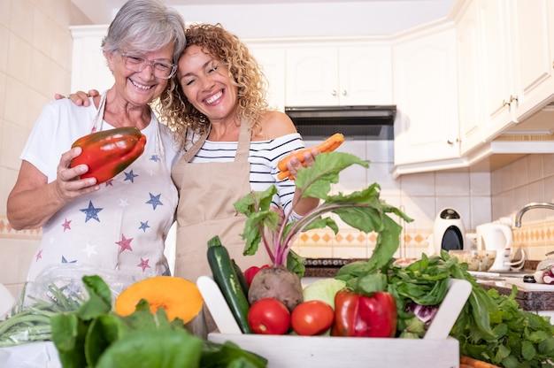 Madre anziana che abbraccia sua figlia in cucina guardando il raccolto sul tavolo. verdure crude, alimentazione sana o dieta