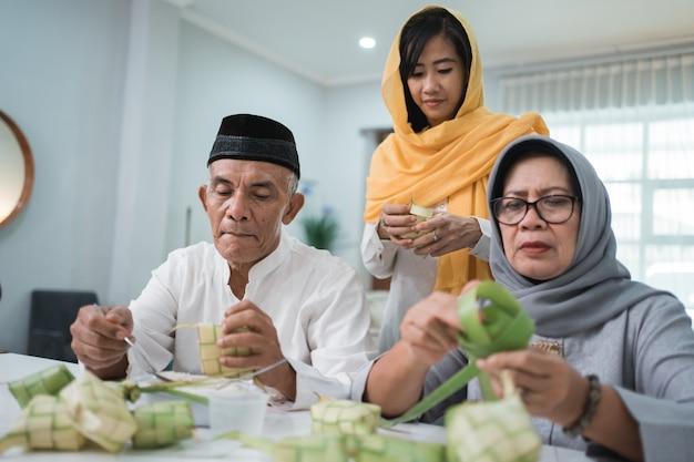 Coppia musulmana senior e figlia che fanno ketupat per la celebrazione di eid fitr mubarak a casa