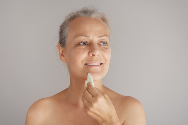 Senior donna nuda si massaggia il viso con una tavola di giada isolata su sfondo grigio