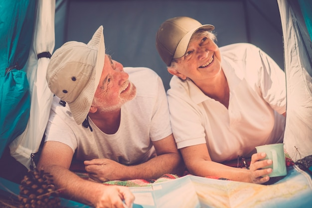 Anziano vecchio viaggiatore alternativo giovane all'interno di una piccola tenda casa godersi il viaggio e la vacanza gratuita con stile campeggio - concetto di avventura e stile di vita felice per pensionati caucasici insieme