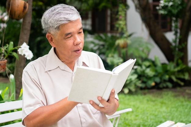 Uomo anziano senior che legge un libro nel parco. concetto di stile di vita pensionistico e hobby.