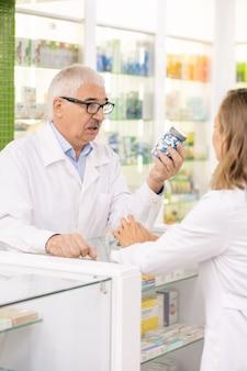 Senior proprietario della farmacia contemporanea che mostra il suo grande vaso subordinato con pillole o additivi biologicamente attivi mentre è in piedi dal contatore