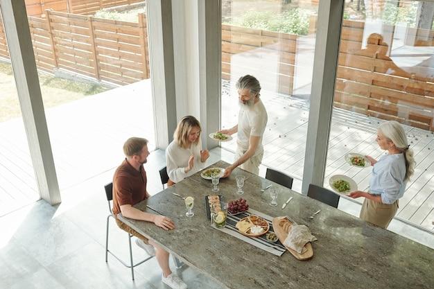 Genitori anziani che servono al tavolo con insalate e snack mentre si prepara per la cena in famiglia con bambini adulti