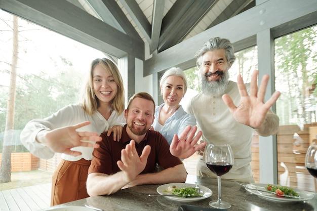 Genitori anziani e figli adulti che agitano le mani sul laptop mentre parlano con i parenti tramite l'app per videoconferenze