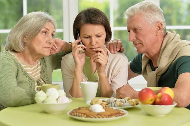 Genitori anziani con figlia preoccupata a casa