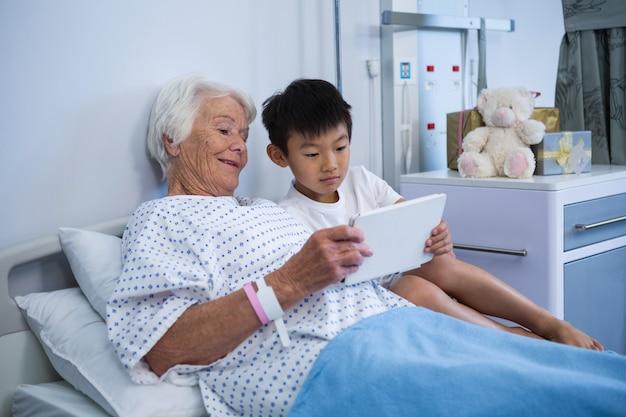 Paziente senior e ragazzo che tengono compressa digitale