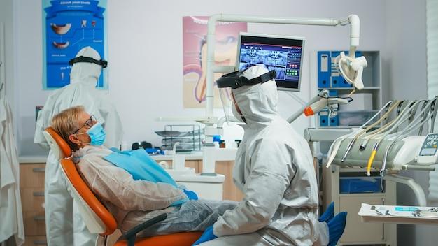 Paziente anziano che parla con il medico dentista vestito con tuta protettiva seduto in clinica stomatologica durante la pandemia di coronavirus. infermiera e ortodontista che indossa tuta, visiera, guanti maschera