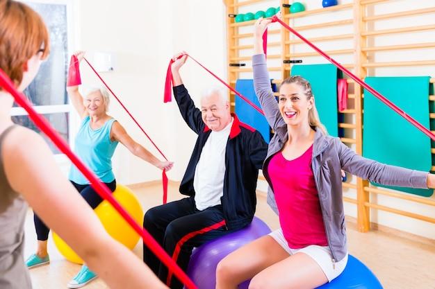 Persone anziane al corso di fitness in palestra che si esercitano con la fascia elastica