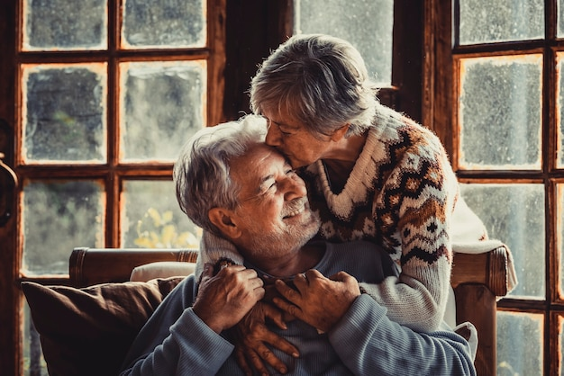 Anziani a casa innamorati che si baciano e si prendono cura l'uno dell'altro. felice relazione uomo maturo e donna insieme. vecchio maschio seduto sul divano e donna anziana che lo abbraccia con cura