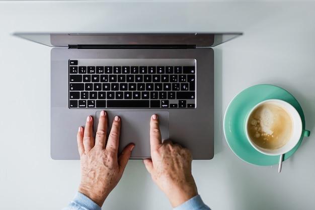 Mani di persone anziane che digitano su un computer portatile