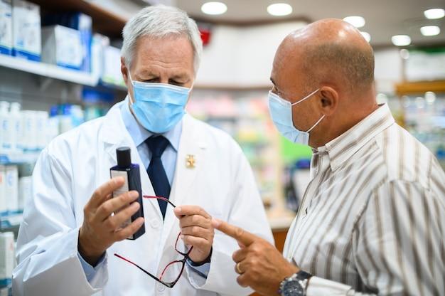 Farmacista senior che ha a che fare con un cliente, entrambi indossano maschere a causa del coronavirus