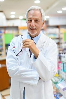 Farmacista senior nel suo negozio sorridendo mentre si tiene gli occhiali