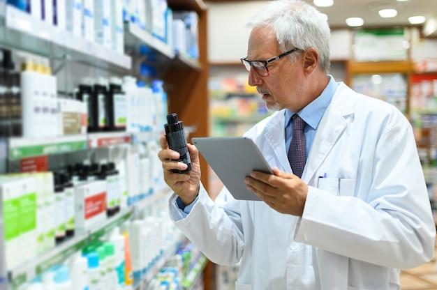 Farmacista senior alla ricerca di un prodotto su uno scaffale e utilizzando un tablet