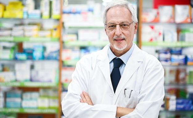 Senior farmacista sorridente e braccia pieghevoli nel suo negozio