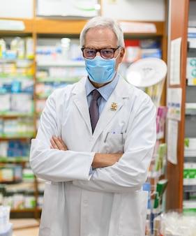 Farmacista senior che indossa una maschera a causa di una pandemia di coronavirus nel suo negozio